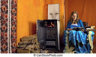 woman read book sitting on armchair at home on cold winter...