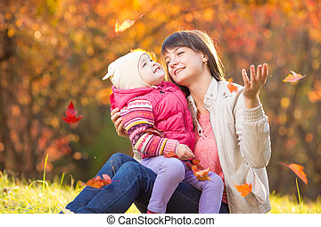 Kid and beautiful mother playing outdoor in autumn park