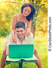 a young smiling happy copule with laptop in park instagram...