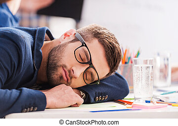 Sleeping at work. Tired young businessman sleeping while sitting at his working place and leaning his head at the desk