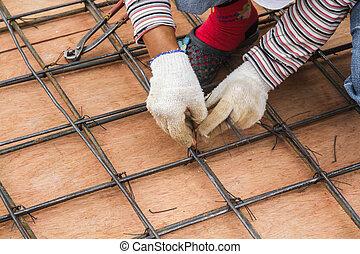 Worker bending steel - Construction workers are steel truss...