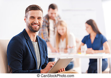 Young and creative. Handsome young man holding digital tablet and smiling while his colleagues discussing something in the background