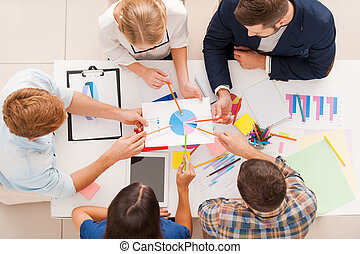 Discussing diagram. Top view of business people pointing diagram together while sitting at the table