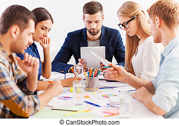 Concentrated on work. Group of confident business people in smart casual wear working together while sitting at the table