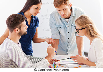 Business discussion. Four cheerful business people in smart casual wear discussing something while leaning at the table