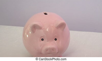 moneybox - human hand throwing a coin into a piggy bank