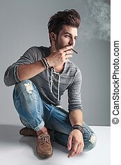 Young fashion man relaxing on the floor while smoking a...