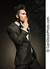 Handsome business man smoking a cigarette while looking away...
