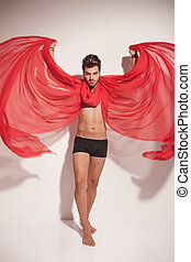 young naked man creating wings with a red textile