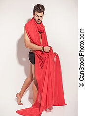 naked man holding a big red textile around him
