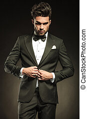 Young elegant business man arranging his tuxedo. - Young...