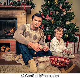 Young father with his son near fireplace in Christmas...