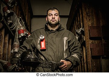 Firefighter in storage room with fire hoses