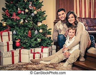 Happy family near Christmas tree in house interior