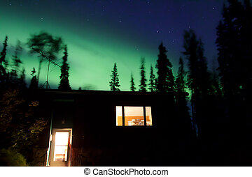 Aurora borealis above house in forest