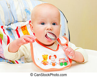 Infant with spoon - Little baby girl sitting in highchair...