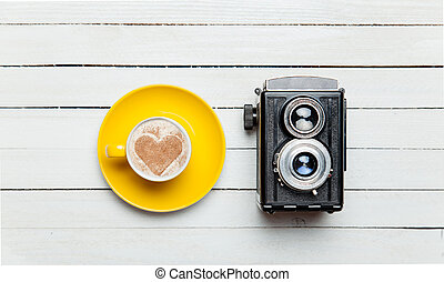 Retro camera and cup of coffee on wooden table