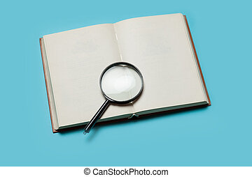 Opened book and loupe on color background