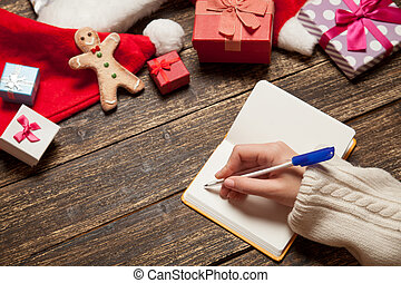 Female writing wish list in to notebook near christmas gifts