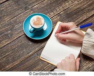Female hand writing something in notebook near cup of...