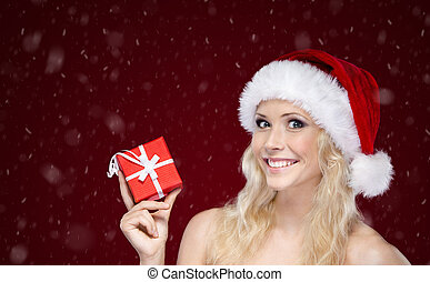 Young woman in Christmas cap hands present