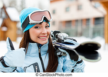 Close up of female handing skis who thumbs up - Close up of...