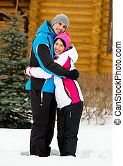 Full-length portrait of embracing couple who wears warm caps...