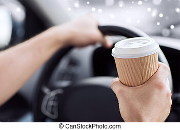close up of man drinking coffee while driving car -...