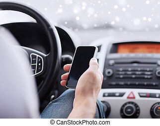 close up of man using smartphone while driving car -...