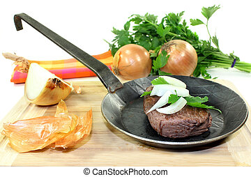 ostrich meat - a piece of ostrich meat in an iron pan