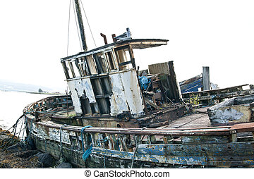 Derelict fishing trawler hauled up and rotting in a sea...
