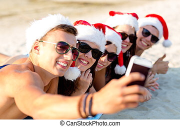 group of friends in santa hats with smartphone - friendship,...