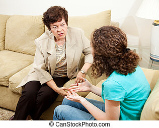Listening to Teen - Caring female therapist counseling a...