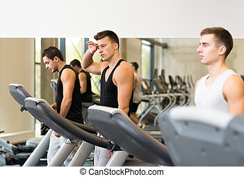 group of men exercising on treadmill in gym - sport,...