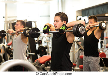 group of men with barbells in gym - sport, fitness,...