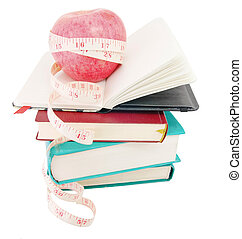 Apple with measure tape on big pile of books - Big ripe red...
