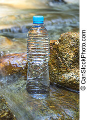 Mineral bottle at water stream in wood forest