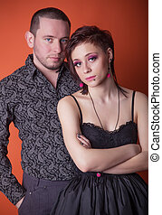 beautiful girl standing next to the young man on a red background