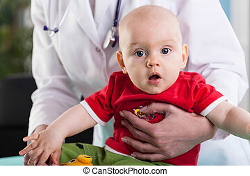 Doctor holding a baby - Caring doctor holding her new baby...