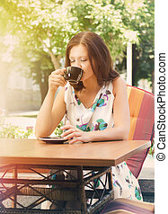 Woman drinking coffee at open-air cafe - Woman seated at a...