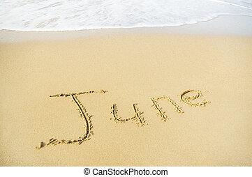 June- written in sand on beach texture