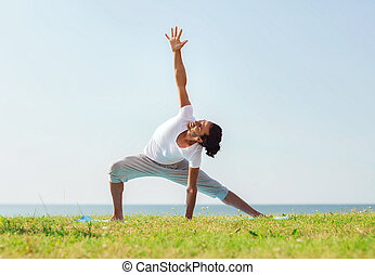smiling man making yoga exercises outdoors - fitness, sport,...