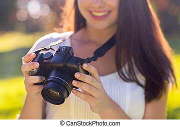close up of young girl with photo camera outdoors -...