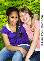 Girl friends - Two teenage girls sitting on grass and...