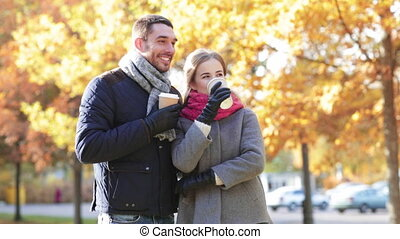 smiling couple with coffee cups in autumn park - love,...