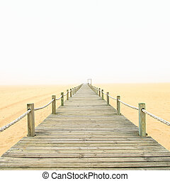 Wooden footbridge on a foggy sand beach background Portugal...