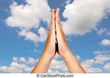 Hands in prayer position against a beautiful sky background