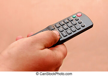 TV remote control in mens hand, a lot of copyspace