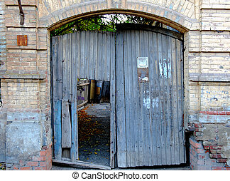 Old wooden gates in brick wall