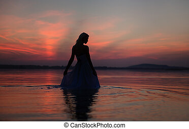 Silhouette of the woman over the sunset background -...